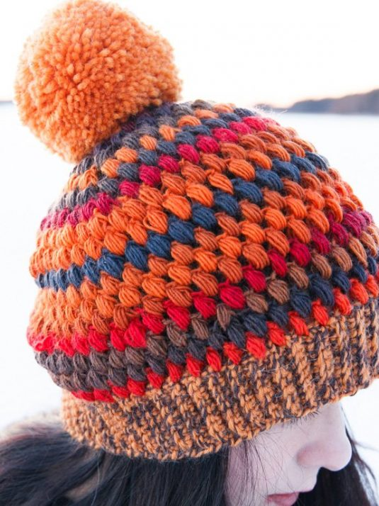 Girl on ice wearing a warm colorful handmade beanie with a pompom