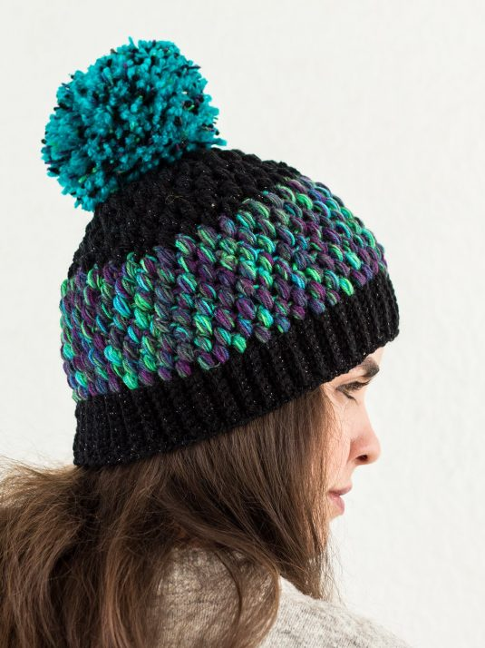 Girl wearing a crocheted beanie with colors inspired by the northern lights