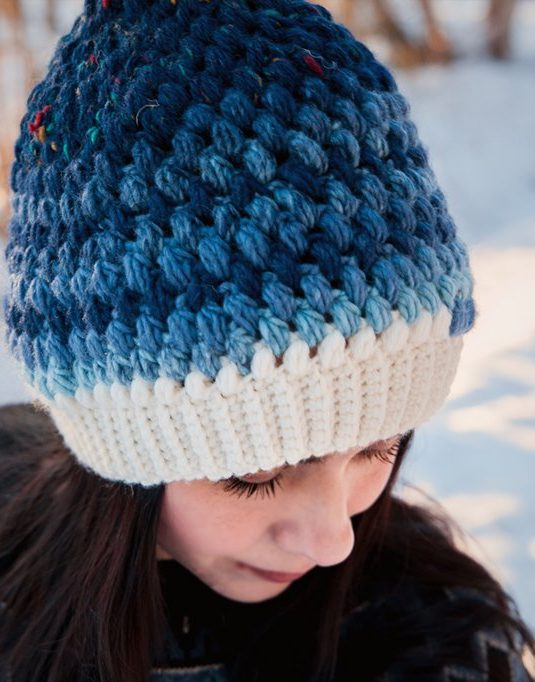 Girl wearning and white and blue woolen beanie.