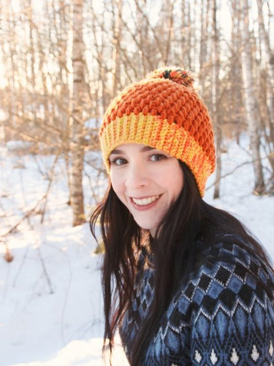 Smiling girl with brown pompom beanie.