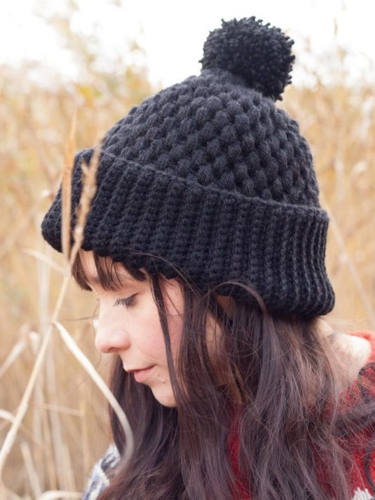 Girl in tall grass wearing a black crochet vegan beanie