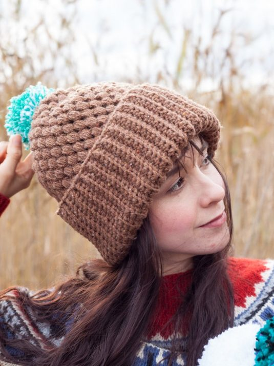 Girl wearing a brown handmade beanie with a mint colored pompom