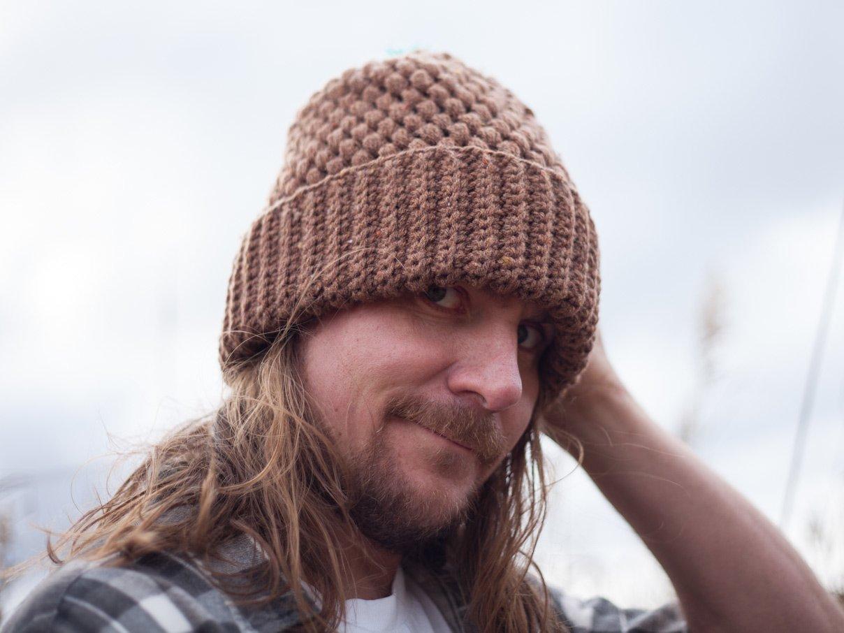 Man with long hear wearing a crocheted beanie
