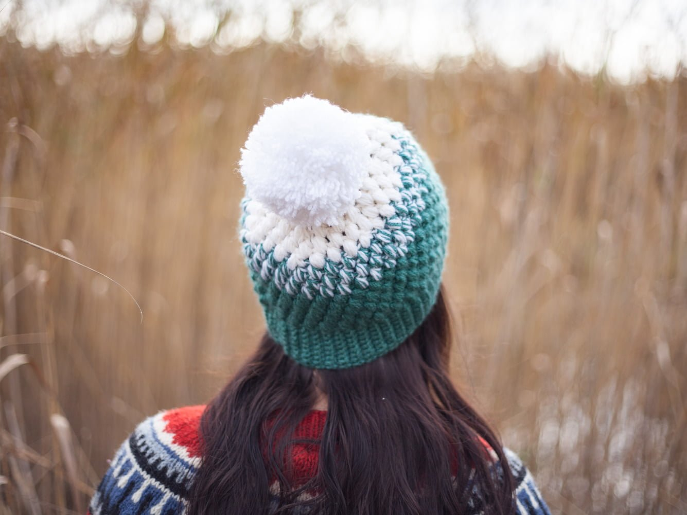 Behind view of girl with mint and white colored pompom beanie