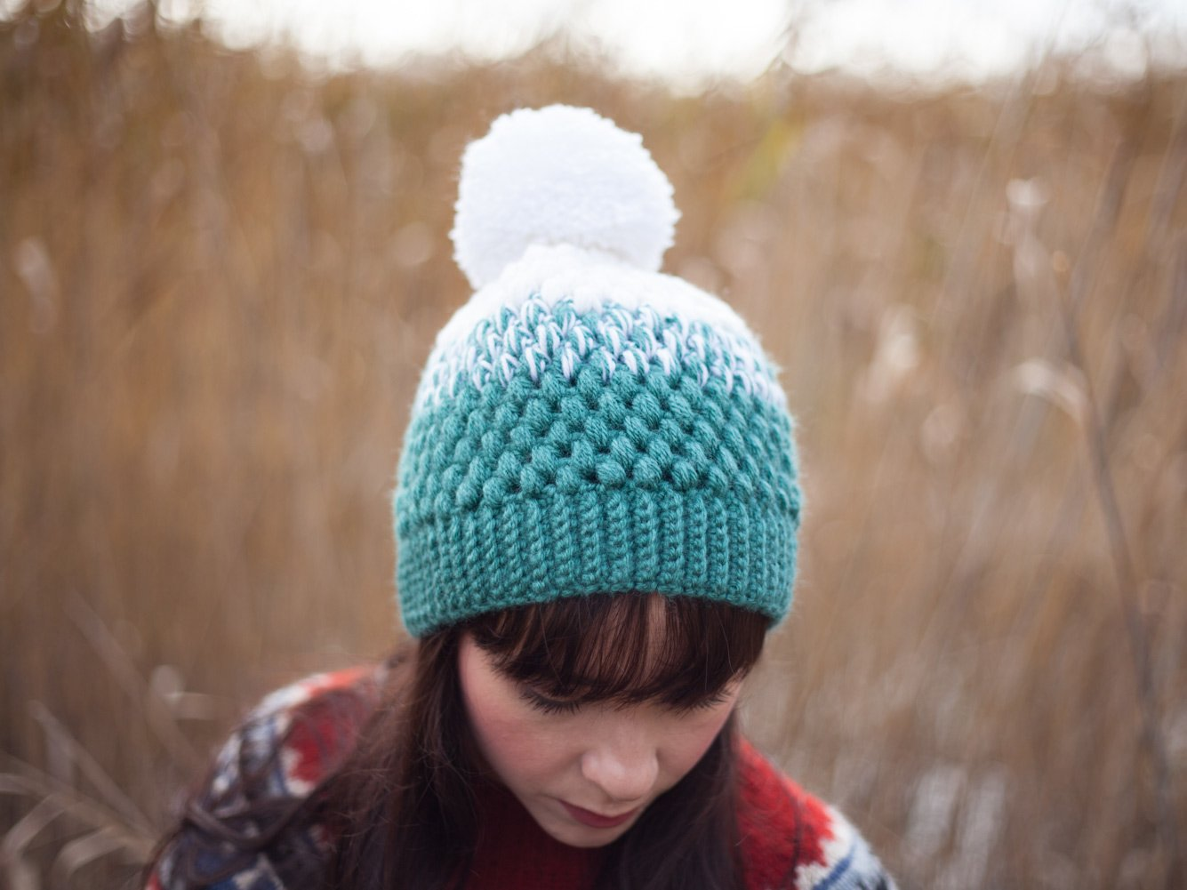 Girl with white mint pompom beanie looking down