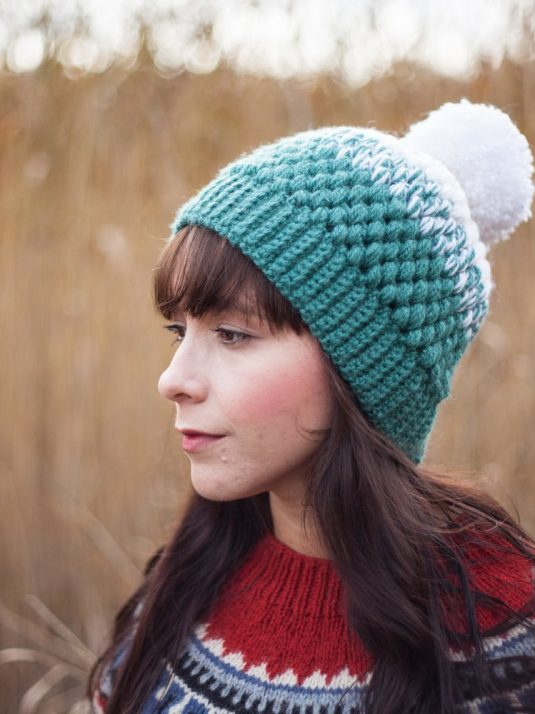 Girl with long dark hair wearing a crocheted pompom beanie looking to the side.