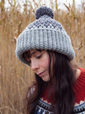Girl with long hair wearing a gray crochet beanie with a pompom