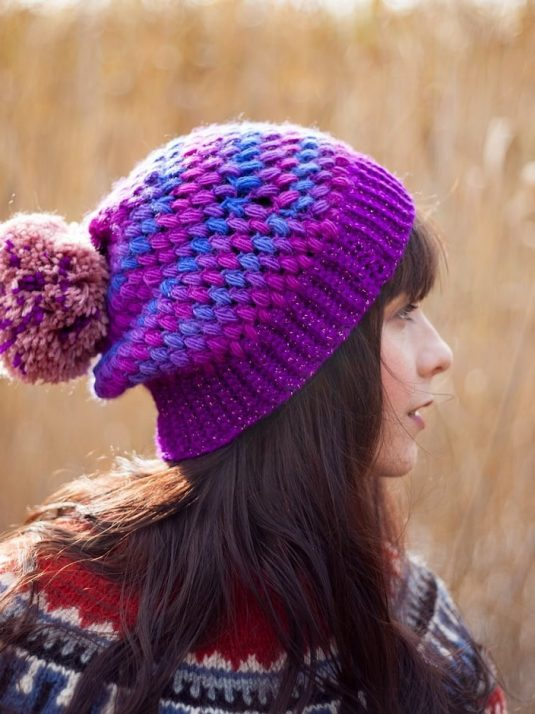 Side view of a girl with a crocheted violet vegan beanie