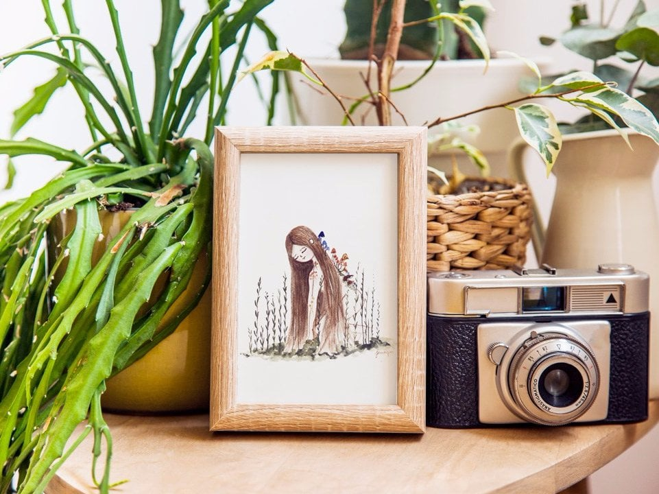 Plant lady watercolor print in a frame surrounded by plants and decoration