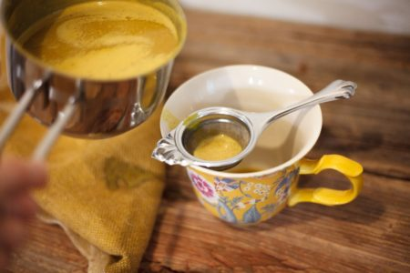 using a strainer to filter turmeric latte