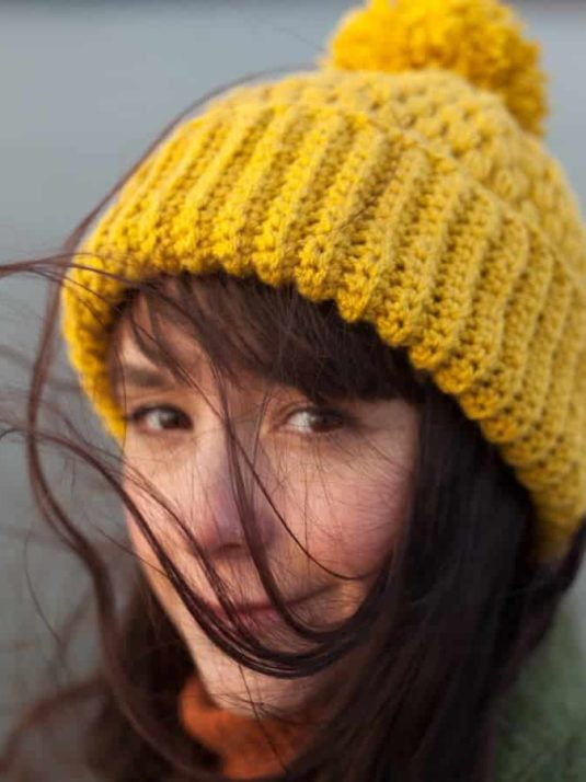 Girl with a mustard colored vegan beanie by Warmsquirrel looking in to the camera