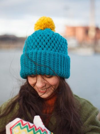 Girl wearing Turquoise color vegan beanie next to a harbour