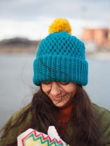 Jennifer Ramirez wearing Turquoise color vegan brimmed beanie next to a harbour