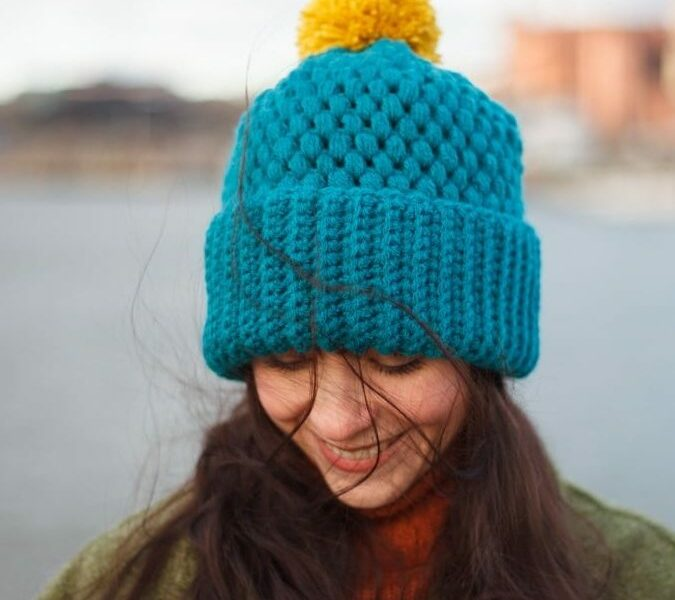 Jennifer Ramirez wearing Turquoise color vegan brimmed beanie next to a harbour