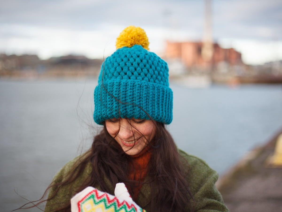Jennifer Ramirez wearing Turquoise color vegan beanie next to a harbour