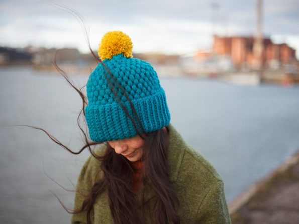 Girl with long hair wearing a turquoise colored vegan beanie with mustard colored pompom by warmsquirrel