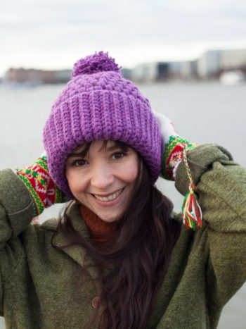 Girl with a vilot colored vegan beanie made by warmsquirrel smiling to the camera