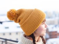 Jenn wearing a mustard vegan beanie with pompom