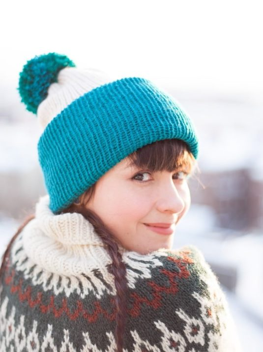 front of Beige and teal vegan beanie with pompom viewed from the side