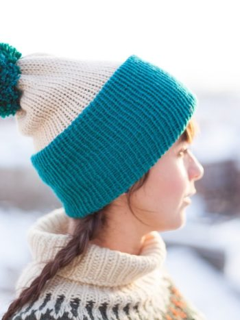 Beige and teal vegan beanie with pompom viewed from the side